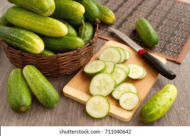 Cucumbers in a wicker bowl on a cutting board. A lot of cucumbers in a wicker cup. Sliced cucumber for cooking. Cucumbers for diet and healthy eating. Fresh vegetables and a knife for slicing.