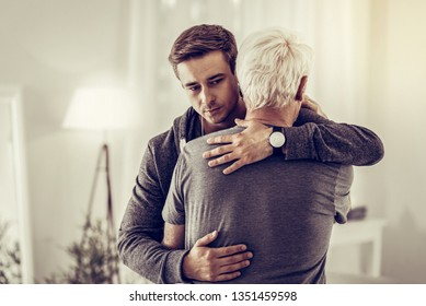 Cuddling sick granddad. Twenty-years-old good-appealing dark-haired kind male calmingly cuddling sick sorrowful aging silver-haired granddad