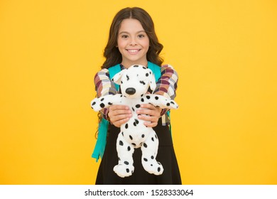 Cuddly dog. Happy small girl hold toy dog yellow background. Little schoolchild smile with soft dog. Adorable dog pet gift. Early learning. Friends and friendship.