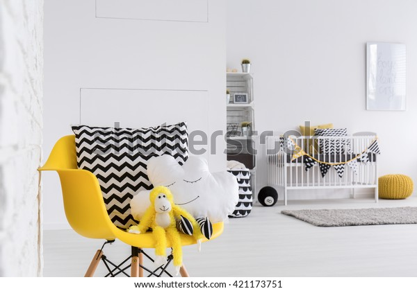 Cuddly mascots seated on a designer chair in a baby room
