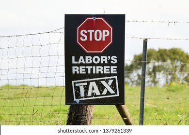 Cudgen / NSW, Australia, April 21 2019:  Sign on a barbed wire fence that says. Stop Labor's retiree tax. White writing on a black background
