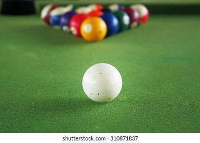 Cue ball on green flannel desk