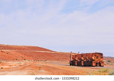 Cue, Western Australia, 20/9/2019. Road train towing four trailers full of iron ore, called D.S.O. or direct shipping ore. Iron ore haul truck, driving between gold mining tailings or dumps.