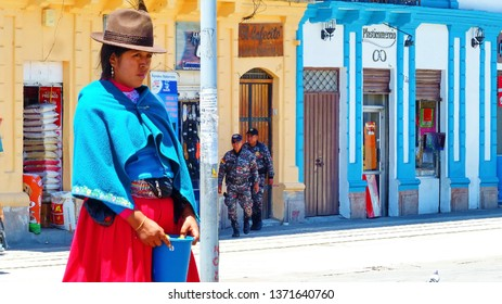 Cuenca, Ecuador - April 5, 2019: Woman Indigenous quechua of Ecuador selling lemons at plaza next to the Mercado