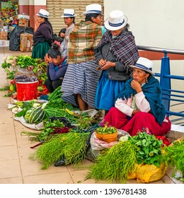 CUENCA, ECUADOR - APRIL 9, 2019: Indigenous ecuadorian women in traditional clothing and Panama hats selling vegetables inside the Cuenca indoor local market.