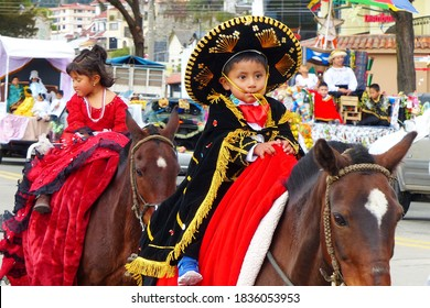 Cuenca, Ecuador- December 24, 2016: Parade Paseo del Nino Viajero which helds on Christmas (Navidad). Little boy dressed up for parade as mexican boy, astride a horse
