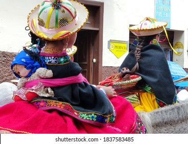 Cuenca, Ecuador - December 24, 2017: Christmas parade Pase del Nino Viajero. Little girls dressed up for parade in embroidered costume. They use traditional way to carry on back baskets or kids