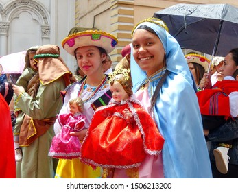 Cuenca, Ecuador - December 24, 2018: Christmas parade Pase del Nino Viajero in honor of baby Jesus. Young women dressed one as Mary and other in national dress carry baby Jesus dolls simbol of parade