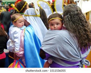 Cuenca, Ecuador - December 24, 2018: Christmas parade in Cuenca city Pase del Nino Viajero (Traveling Child) in honor of baby Jesus. Woman carries baby dressed as angel
