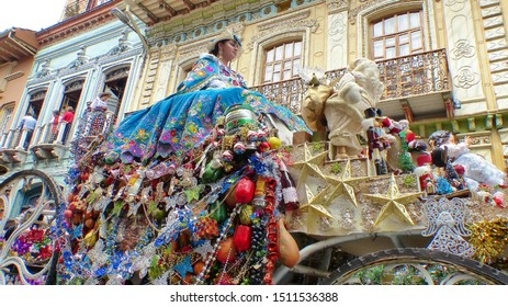 Cuenca, Ecuador - December 24, 2018: Christmas parade Pase del Nino Viajero. Woman dressed up for parade in rich colorful traditional costume with embroidery rides a coach with christmas decoration