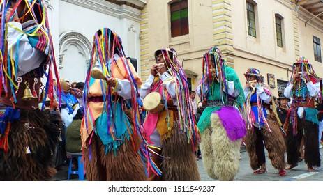Cuenca, Ecuador - December 24, 2018: Christmas parade in Cuenca city Pase del Nino Viajero (Traveling Child) in honor of baby Jesus. Group of indigenous cayambe men dance durante parade