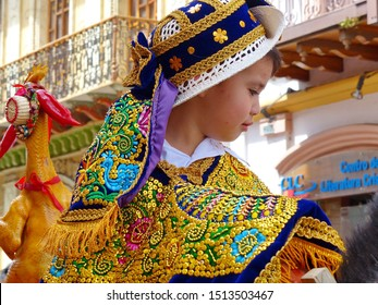 Cuenca, Ecuador- December 24, 2018: Christmas parade Paseo del Nino Viajero (Traveling Child). Little boy dressed up for parade in embroidered costume riding horse decorated with roasted chicken