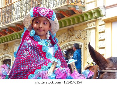 Cuenca, Ecuador - December 24, 2018: Christmas parade Paseo del Nino Viajero (Traveling Child). Girl dressed up for parade in embroidered costume riding horse