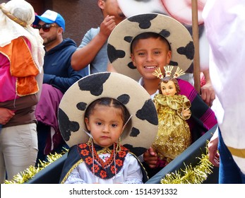Cuenca, Ecuador - December 24, 2018: Christmas parade Paseo del Nino Viajero (Traveling Child). Children boy and girl in national costumes of Saraguro, Loja province, carry doll of Jesus Christ