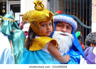 Cuenca, Ecuador - December 24, 2018: Christmas parade Paseo del Nino Viajero (Traveling Child) in honour of baby Jesus. Little girl as egyptian queen and man as Wise man - heroes of Bible stories