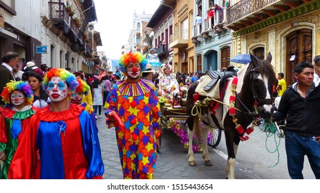 Cuenca, Ecuador - December 24, 2018: Christmas parade Pase del Nino Viajero. Clowns in colorful costumes and woman in traditional costume with embroidery rides a coach with christmas decoration