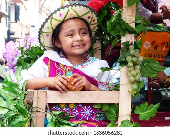Cuenca, Ecuador - December 24,2016: Portrait of little girl dressed up  in colorful embroidered costume for Christmas parade Pase del Nino Viajero (Traveling Child) smiles to audience