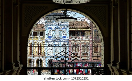 Cuenca, Ecuador - February 15, 2019: View through the arch and decorative lattice on colonial style residential buildings located on the San Francisco Plaza in Cuenca