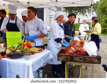 Cuenca, Ecuador - October 31, 2018: Festival Colada Morada y Guaguas de Pan. Young people, students, present food and  traditional roasted pig at local feria