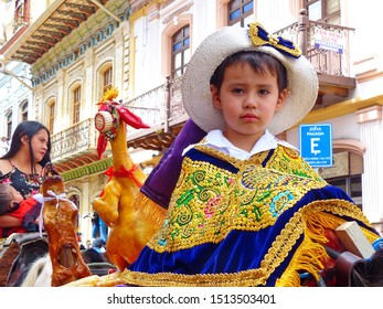 Cuenca, Ecuador-December 24, 2018: Christmas parade Paseo del Nino Viajero (Traveling Child). Little boy dressed up for parade in embroidered costume riding horse decorated with chicken and guinea pig