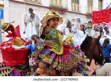 Cuenca, Ecuador-December 24, 2018: Christmas parade Paseo del Nino Viajero (Traveling Child). Little girl dressed up for parade in embroidered costume riding decorated horse and chicken in basket