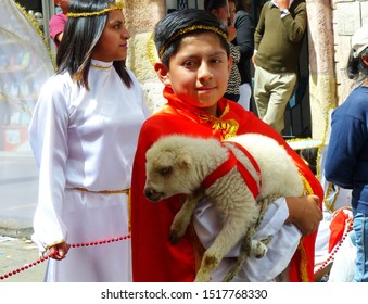 Cuenca, Ecuador-December 24, 2018: Christmas parade Paseo del Nino Viajero (Traveling Child) in honour og baby Jesus. Boy carries little lamb