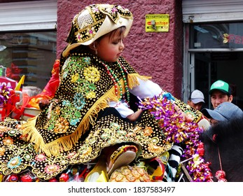 Cuenca, Ecuador-December 24, 2018: Christmas parade Pase del Nino Viajero (Traveling Child). Little girl dressed up for parade in embroidered costume riding horse decorated  with different food