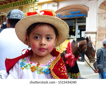 Cuenca, Ecuador-December 24,2018: Portrait of little girl dressed up for Christmas parade Pase del Nino Viajero (Traveling Child) in colorful embroidered costume and straw hat typical for this event