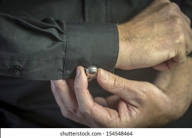 Cuff Link/ a close up of a man getting dressed in formal attire with a jewelled cuff link on a black shirt's sleeve