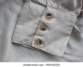 Cuffs. Beige three-button cuff on a grey organic linen shirt. Details of natural clothing. Comfortable style cloth.