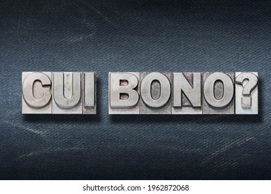 cui bono (to whose benefit) question made from metallic letterpress on dark jeans background