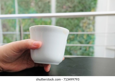 Cuisine and Food, Hand Holding An Empty Cup After Drinking Coffee on The Table.