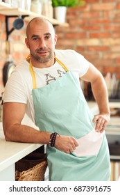 Cuisine. Man at kitchen in blue apron