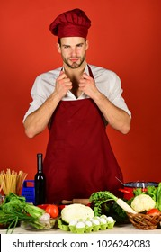 Cuisine and professional cooking concept. Man in cook hat and apron adjusts collar. Cook works in kitchen near table with vegetables and tools. Chef with sexy face poses in uniform on red background.