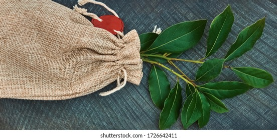 Culinary background in blue with a fabric bag in which a bouquet of twigs of fresh green laurel