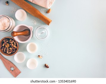Culinary background. Cooking utensils, a whisk, a rolling pin, cupcake pans, a wooden bowl and baking ingredients. Bakery background frame. Top view, copy space.