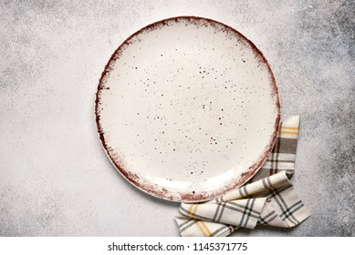 Culinary background with empty plate and napkin on a grey slate, stone or concrete table.Top view with copy space.