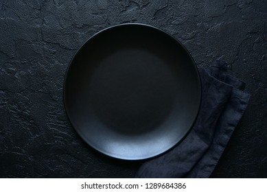 Culinary background with empty plate and napkin on a black slate, stone or concrete table.Top view with copy space.