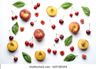 Culinary background, food blog, recipe concept. Layout of ripe sweet cherries and peaches on white. Seasonal dessert. Delicious vegetarian meals and diet concept