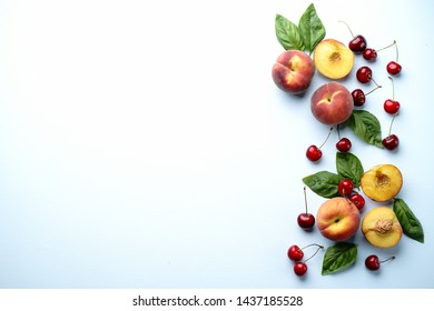 Culinary background, food blog, recipe concept. Layout of ripe sweet cherries and peaches on blue table. Seasonal dessert. Delicious vegetarian meals and diet concept