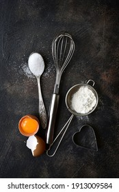 Culinary background with ingredients for baking : flour, egg and sugar on a dark slate, stone, concrete or metal background. Top view with copy space.