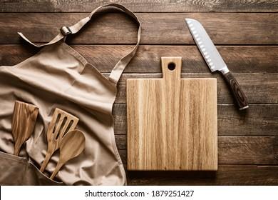 Arrière-plan culinaire, ustensiles de cuisine et tablier sur le plan de la cuisine avec place blanche pour tout texte de recette ou de menu
