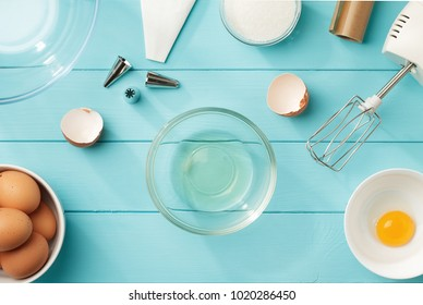 Culinary background with separated egg whites and yolks in the bowls on blue wooden table. Step by step recipe of meringue cookies top view.