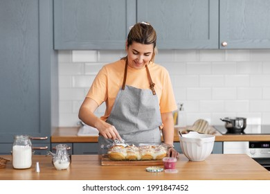 culinary, bake and cooking food concept - happy smiling young woman adding buttercream topping to baked roll buns in baking dish on kitchen at home