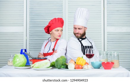 Culinary battle concept. Woman and bearded man culinary show competitors. Who cook better. Ultimate cooking challenge. Culinary battle of two chefs. Couple compete in culinary arts. Kitchen rules.