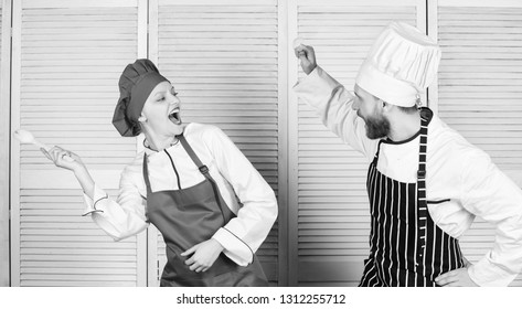 Culinary battle concept. Woman and bearded man culinary show competitors. Ultimate cooking challenge. Culinary battle of two chefs. Couple compete in culinary arts. Kitchen rules. Who cook better.