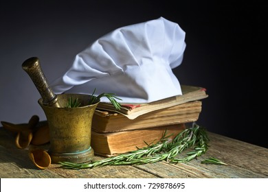 Culinary books , chef hat and wooden spoons . Kitchen accessories on the old wooden table .