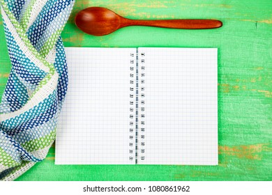Culinary recipe, towel and spoon on a green wooden table. Cooking. Menu.