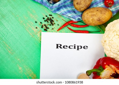 Culinary recipe, towel, spoon and various vegetables on a green wooden table. Cooking. Menu.