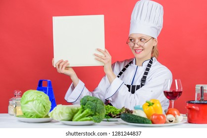 Culinary school concept. Female in hat and apron knows everything about culinary arts. Traditional cuisine. Culinary expert. Woman chef cooking healthy food. Girl read book top best culinary recipes.